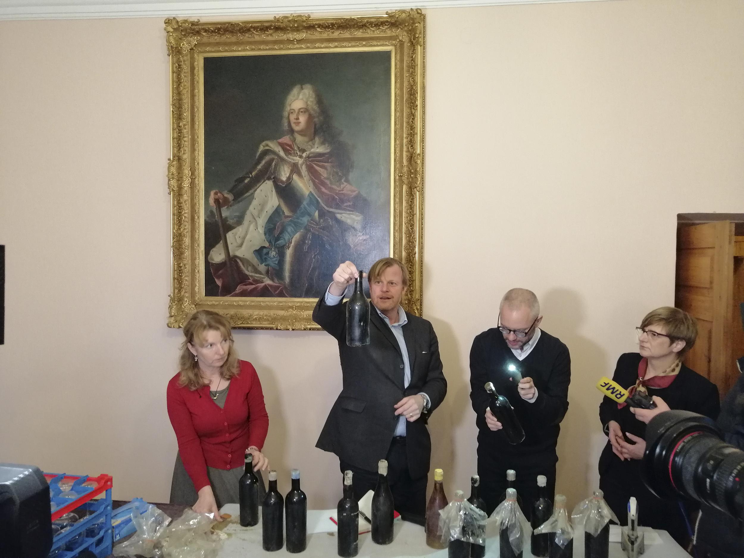 Fotografia. Konferencja prasowa. Dwie kobiety i między nimi dwaj mężczyźni stojący za stołem, na którym ustawione są zakurzone i zabezpieczone folia butelki z winem. Jeden z mężczyzn trzyma wysoko butelkę i przygląda się jej z zaciekawieniem, drugi nachylony przygląda się butelce podświetlając ją latarką.