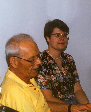 Fotografia, mężczyzna i kobieta w ujęciu do pasa. Mężczyzna starszy, siwiejący i lekko łysiejący, ubrany w żółtą koszulkę typu polo i młoda, krótkowłosa kobieta w okularach ubrana w kwiecista bluzkę z krótkim rękawem, na szyi perły.