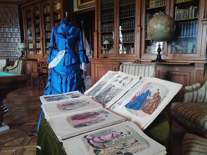 """Fragment pomieszczenia z szafami bibliotecznymi. Na ich tle manekin ubrany w stylową suknię. Na pierwszym planie kilka numerów dziewiętnastowiecznego czasopisma modowego """"La Mode Illustrée. Journal de la Famille"""""""