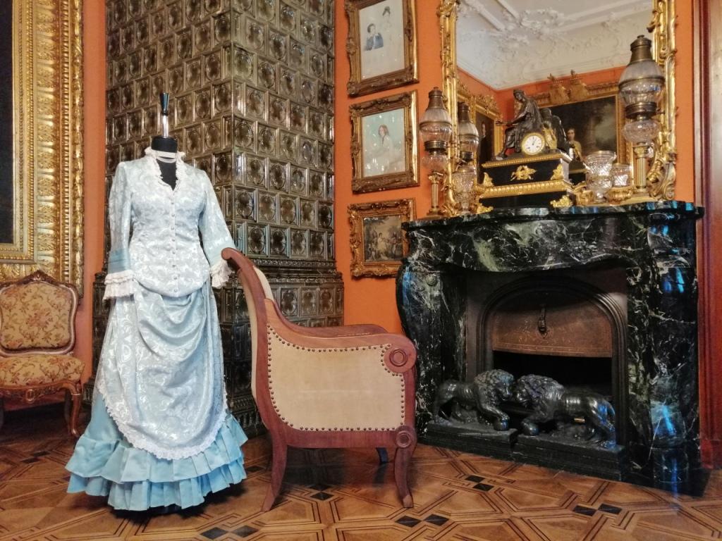 Fotografia. Fragment pomieszczenia. Przy jasnym fotelu ustawionym przed kominkiem z zielonego marmuru dziewiętnastowieczna stylizowana suknia zaprezentowana na manekinie. W tle wysoki piec z oliwkowych kafli. Suknia składa się ze stanika i dwuczęściowej spódnicy. Spodnia jej część uszyta jest z jednobarwnego seledynowego materiału wykończonego u dołu dwurzędową, plisowaną falbanką. Górna warstwa, drapowana na biodrach wykonana jest z jaśniejszego materiału z kwiatową aplikacją. Z tej samej tkaniny uszyty jest też stanik. Długie rękawy zakończone są delikatną koronką. Tak samo obszyty jest dekolt i górna warstwa spódnicy.