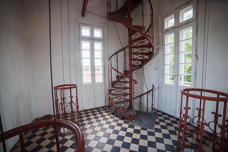 Fotografia pozioma. Po lewej i prawej stronie zdjęcia znajdują się dwa napędy zegara zwane wagami.  W centrum widać czerwone , kręte schody z ozdobną balustradą. Po obu stronach schodów dwie pary białych, podwójnych drzwi balkonowych. Całość dopełnia czarno-biała podłoga przypominająca szachownicę.