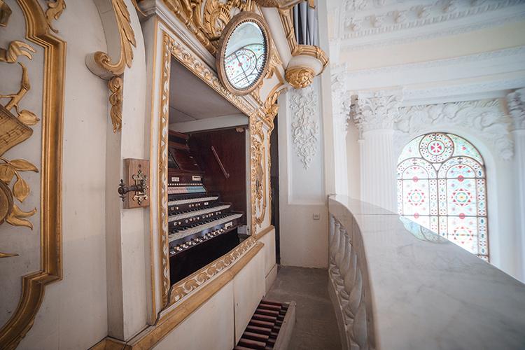 Fotografia pozioma. Na podwyższeniu znajdują się organy w jasnych wnękach z pozłacanymi dekorami. W tle zdjęcia duży witraż okienny z geometryczną dekoracją.